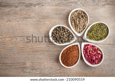 A colorful assortment of loose teas in petal shaped bowls on a wooden background with copyspace - stock photo