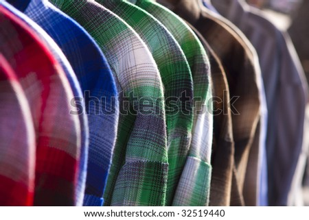 A colorful assortment of plaid shirts on a rack.