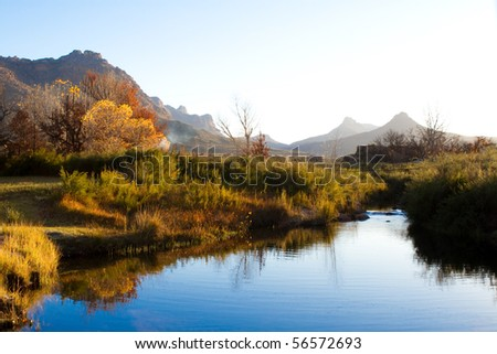 A colorful autumn scene next to a river - stock photo