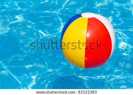 A colorful beach ball floating in a blue swimming pool
