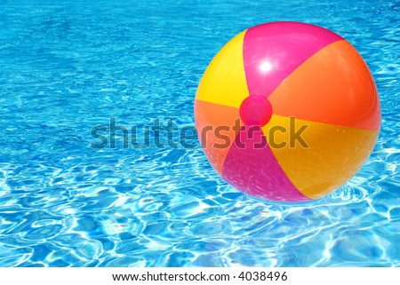 A colorful beach ball floating on the  swimming pool.