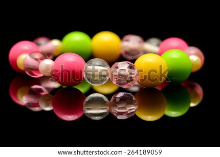 A colorful beaded bracelet isolated on black background - stock photo