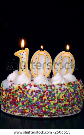 A colorful birthday cake with candles shaped like the number 100. Black background. - stock photo