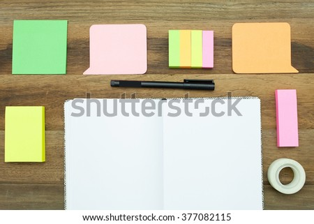A colorful blank post it paper around a book with wooden background