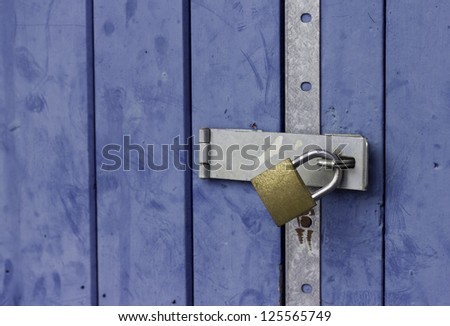 A colorful blue door with a sturdy looking gold padlock attached - stock photo