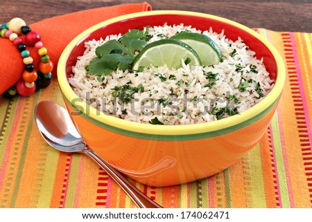 A colorful bowl of basmati rice and cilantro, garnished with fresh lime slices. - stock photo