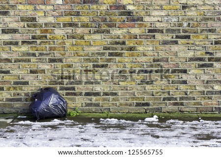 A colorful brick wall with a single garbage sack leaning against it - stock photo