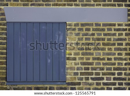 A colorful brick wall with a small pleasing slatted blue door in it and a clean blue/grey beam across the top - stock photo