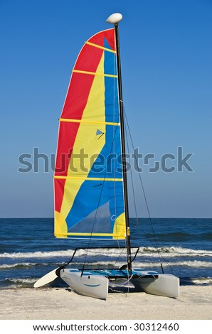 A colorful catamaran rental sailboat at a resort.