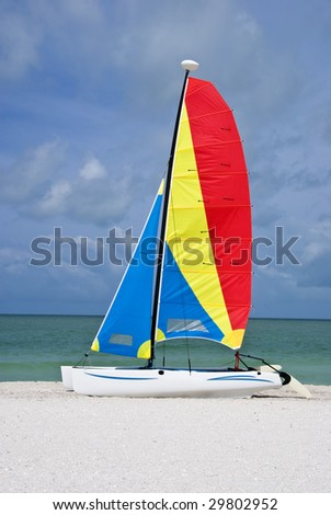 A colorful catamaran sailboat on a beautiful beach, with turquoise sea and blue sky in the background. - stock photo