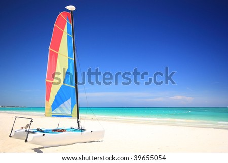 A colorful catamaran sailboat on a gorgeous tropical beach. Travel & tourism collection. - stock photo