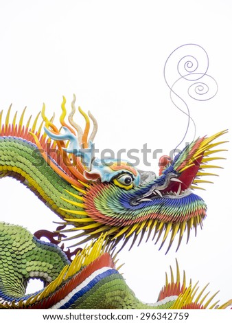 a colorful chinese dragon on white background, the dragon have green and yellow flakes with red and yellow fins. the dragon long mustaches point up toward sky. its left leg stretch upward. - stock photo