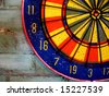 A colorful dartboard is displayed on a brick wall.  Horizontally framed photo. - stock photo