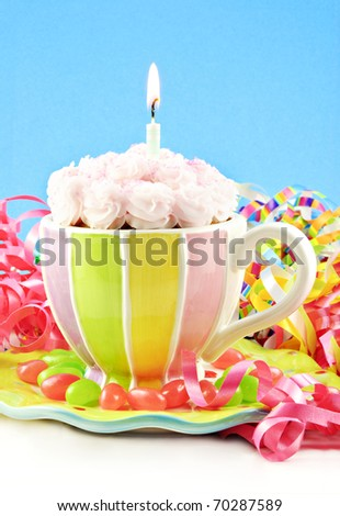 A colorful homemade birthday cupcake in a cup with one lit candle, blue vertical background with copy space - stock photo