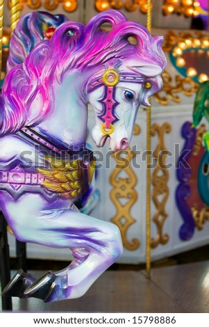 A colorful horse close-up on a carousel at the fair ground - stock photo