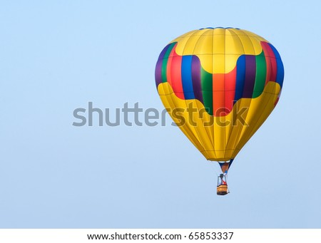 A colorful hot air balloon floating and flying against a blue sky. - stock photo