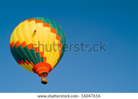 A colorful hot air balloon floating in a bright blue sky.