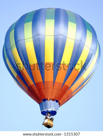 A colorful hot air balloon in a bright blue sky - stock photo