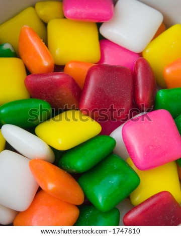 A colorful image of tiny pieces of different colored, candy coated gum (think chicklets).  The small pieces of gum fill up almost the entire image, so shot could also be used as a textured background. - stock photo