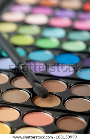 A colorful image on an eyeshadow pallet with a brush.