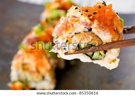 A colorful Japanese sushi roll being held in the air chopsticks over a plate.  Asian food is delicious! - stock photo