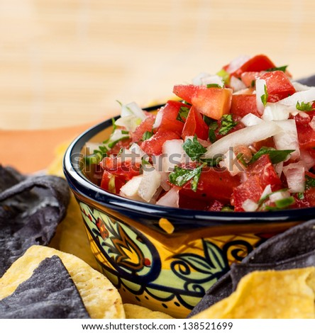 A colorful mexican style ceramic bowl filled with pico de gallo - stock photo