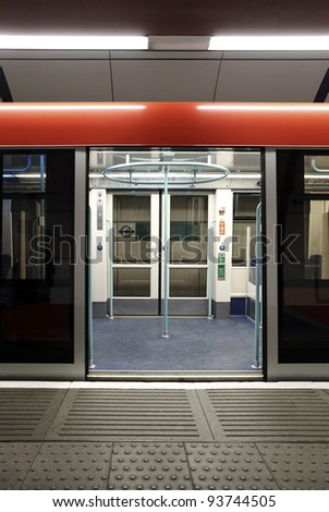 A colorful opened sliding mechanical door of the London Underground train at a tube station waiting for passenger. - stock photo