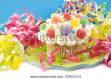 A colorful party cupcake with bright colored party decorations, horizontal with copy space, selective focus