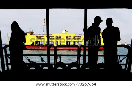 A colorful passenger ferry sailing past a boat jetty with silhouette of a group of tourists. - stock photo