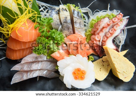 A colorful platter of sashimi sushi with tuna and crab sticks in foreground - stock photo