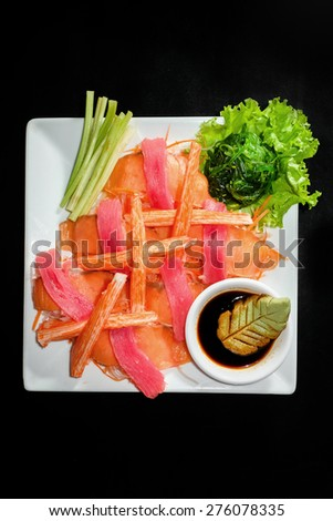A colorful platter of sashimi sushi with tuna and crab sticks in foreground and cucumber decorations in black background - stock photo