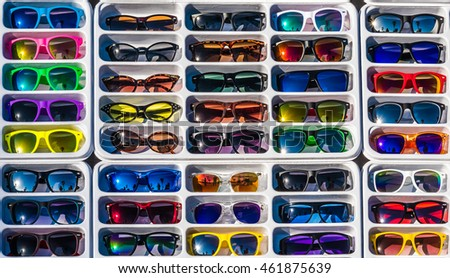 A colorful rack of sunglasses are on display.