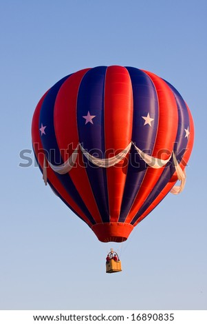 A colorful red, white, and blue patriotic (USA) hot air balloon at a festival is suspended in mid-air on a beautiful clear day. - stock photo