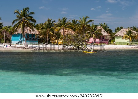A colorful resort is built on the edge of a sandy island in the Caribbean Sea. This region is a popular vacation destination for kayakers, divers, snorkelers, and recreational fishermen. - stock photo