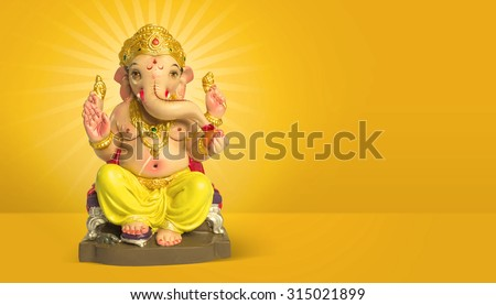 A colorful statue of Ganesha Idol on plain bright yellow background. Clear space for text or headline. - stock photo