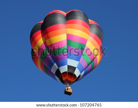 A colorful striped hot air balloon against a blue sky. Taken at the Albuquerque Balloon Fiesta in New Mexico - stock photo