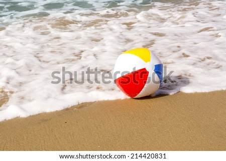 A colorful, summertime beach ball washes up to a sandy beach while being pushed by the ocean??s gentle, foamy surf.