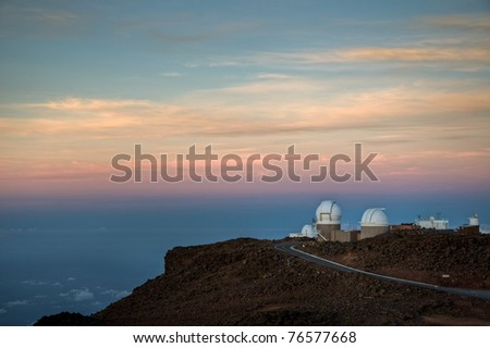A colorful sunrise on the observatories of Science City on the summit of Haleakala, Maui, Hawaii. - stock photo