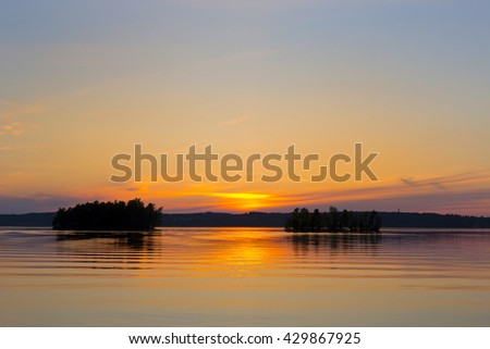 A colorful sunset by the lake in Finland. Image taken during sundown. Image has some saturation added.