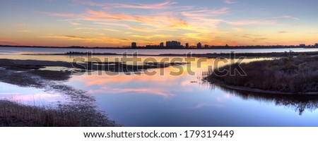 A colorful sunset reflected in the inlet at Big lagoon State Park, with Perdido Key, Florida silhouetted in the background. - stock photo