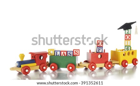"A colorful toy train hauling alphabet blocks arranged to spell out ""Class of 2016,"" a graduation cap on the last blocks.  On a white background.  - stock photo"