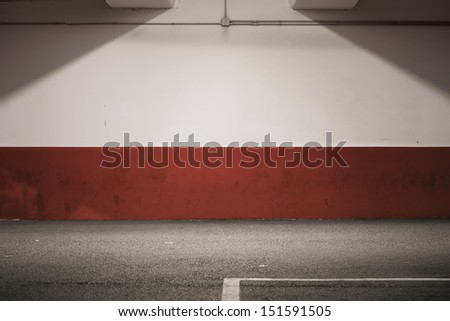 A colorful wall of car park lit from above. Red on the bottom, white on the top. Asphalt with a piece of line. - stock photo