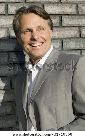A colour portrait of a handsome smiling man in a smart suit. - stock photo