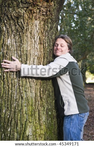 A colour portrait photo of a happy smiling forties man hugging a tree in the forest. - stock photo