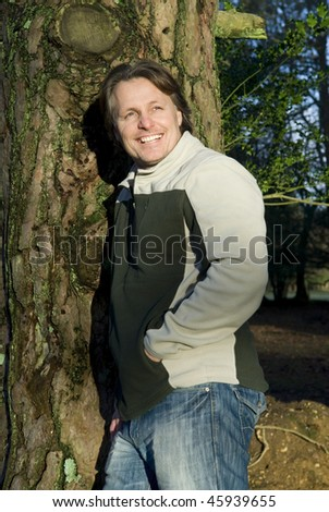A colour portrait photo of a happy smiling forties man leaning adainst a tree in the forest