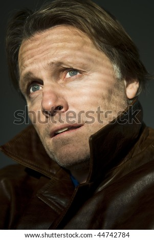 A colour portrait photo of a pensive and anxious looking forties man looking towards the blinds of his window - stock photo