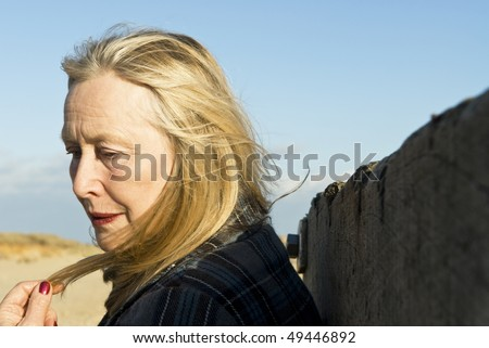 A colour portrait photo of a pensive thoughtful looking older woman in her sixties playing with her hair. - stock photo