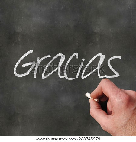 A Colourful 3d Rendered Concept Illustration showing a hand writting Gracias on a blank blackboard - stock photo