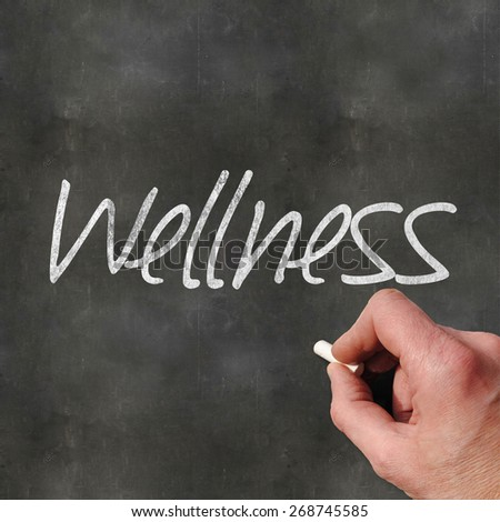 A Colourful 3d Rendered Concept Illustration showing a hand writting Wellness on a blank blackboard - stock photo