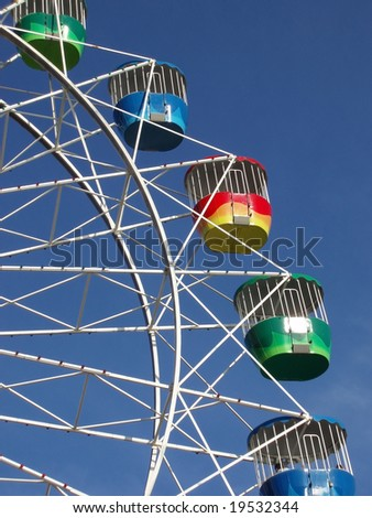 a colourful fairground wheel against a blue sky